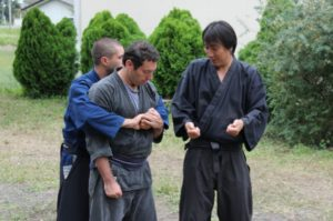 Kiyomoto (left) teaches how to strike back when assaulted from behind.